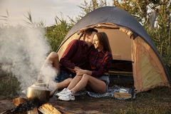 Young couple resting in nature with a tent near the fire stock image