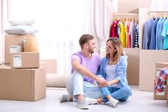 Young couple resting near wardrobe boxes. On moving day Stock Images