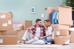 Young couple resting near wardrobe boxes. On moving day Stock Image