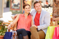 Young Couple Resting With Shopping Bags Sitting In Mall Royalty Free Stock Images