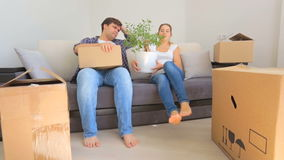Young couple resting on sofa after moving to their new house. Young couple resting on sofa after moving to new house stock video footage
