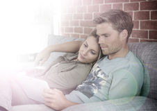 Young couple resting on a sofa and watching a film on a tablet Royalty Free Stock Image