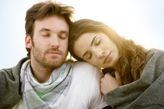 Young couple resting in summer sunshine. Romantic young couple sitting and resting with closed eyes in summer sunshine royalty free stock photos