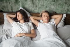 Young couple resting sleeping well together in comfortable bed. Young couple resting together with eyes closed sleeping well in comfortable bed before waking up Royalty Free Stock Images