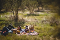 Young couple resting together on picnic blanket at olive farm Royalty Free Stock Images