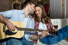 Young couple resting together on sofa with acoustic guitar and red wine Royalty Free Stock Photo