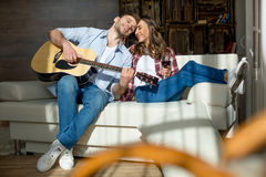 Young couple resting together on sofa with acoustic guitar and red wine Royalty Free Stock Photography