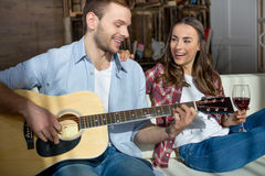 Young couple resting together on sofa with guitar and wine Royalty Free Stock Photo
