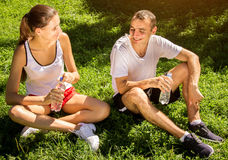 Young couple resting after training and drinking water Royalty Free Stock Photography