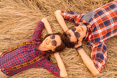 Young couple rests on dry grass Royalty Free Stock Photography