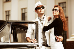 Young fashion couple in love next to retro car Stock Photography