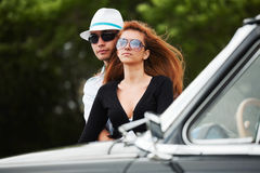 Happy young fashion couple in love by retro car Royalty Free Stock Photos