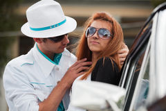 Young fashion couple in love at the retro car. Young fashion man and woman flirting at the retro car Royalty Free Stock Image