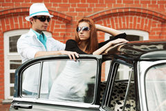 Happy young fashion couple in love by retro car Royalty Free Stock Photography