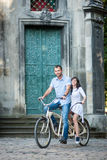Young couple on retro tandem bicycle at the street city Stock Photography