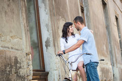 Young couple on retro tandem bicycle at the street city Royalty Free Stock Image