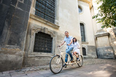 Young couple on retro tandem bicycle at the street city Stock Images
