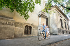 Young couple on retro tandem bicycle at the street city Royalty Free Stock Photography