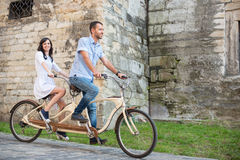 Young couple on retro tandem bicycle at the street city Stock Photos