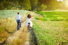 Young couple ride bicycles in the meadow Stock Photo