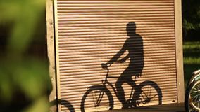 A young couple rides a bicycle and a beautiful shadow is seen on the wall. sunset. Summer stock footage
