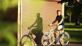A young couple rides a bicycle and a beautiful shadow is seen on the wall. sunset. Summer stock video footage