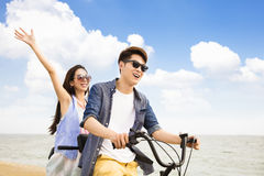 Young couple riding bicycle on the beach. Happy young couple riding bicycle on the beach stock photos