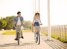 Young couple riding on bicycle in city park Royalty Free Stock Images