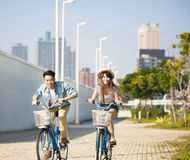 young couple riding on bicycle in city park Stock Photos