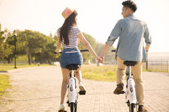 Young couple riding on bicycle in city park Stock Image