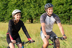 Young Couple Riding Bicycle In Meadow Royalty Free Stock Image