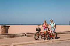Young couple riding bicycles down the Venice beach in Los Angeles. Near Santa Monica pier Stock Photo