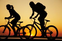 Young couple riding bicycles at sunset. Young couple riding bicycles on the beach at sunset. Silhouettes Royalty Free Stock Photos