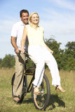 Young couple riding bike in countryside royalty free stock photo