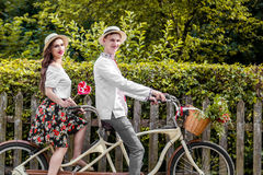 Young couple riding a bike tandem in the park Royalty Free Stock Photo