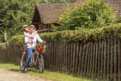 Young couple riding a bike tandem in the park Stock Photo