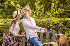 Young couple riding a bike tandem in the park. Against the background of the fence from the tree Stock Photos