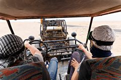 Young couple riding buggy car in desert Stock Photo