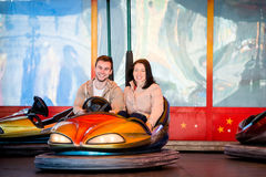 Young couple riding car in amusement park Stock Images