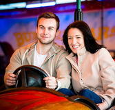 Young couple riding car in amusement park Royalty Free Stock Images