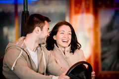 Young couple riding car in amusement park Royalty Free Stock Image