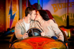 Young couple riding car in amusement park Stock Photography