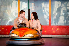 Young couple riding car in amusement park Royalty Free Stock Photo