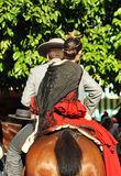 Young couple riding at horse in the Seville Fair, feast in Spain Royalty Free Stock Photo