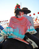 Young couple riding at horse in the Seville Fair, feast in Spain Stock Image