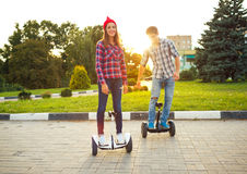 Young couple riding hoverboard - electrical scooter, personal ec Royalty Free Stock Photo