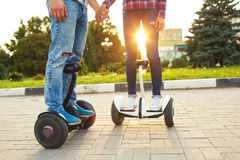 A young couple riding hoverboard - electrical scooter, personal. Eco transport, gyro scooter, smart balance wheel. New modern technologies royalty free stock photography