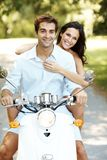 Young couple riding on moped in a park Royalty Free Stock Image