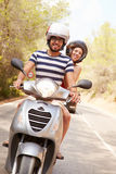 Young Couple Riding Motor Scooter Along Country Road Stock Images