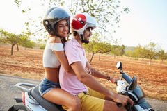 Young Couple Riding Motor Scooter Along Country Road Royalty Free Stock Image